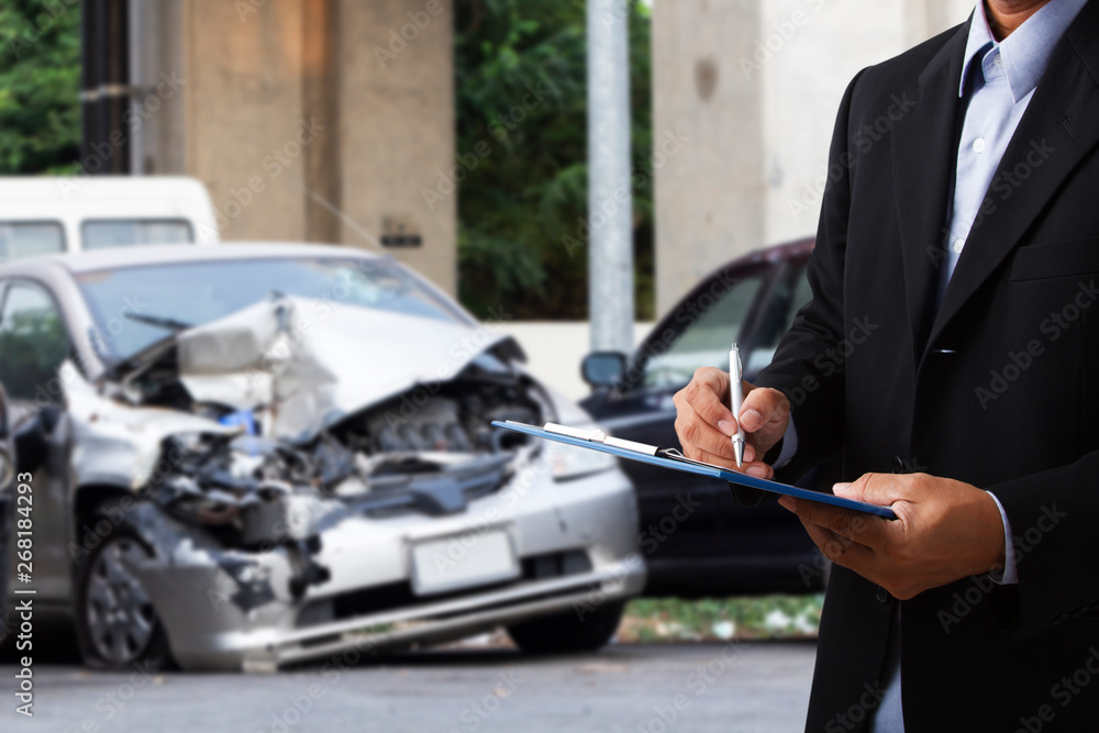 Fototapety, obrazy: Car insurance officer writing on clipboard while insurance agent examining black car after accident.