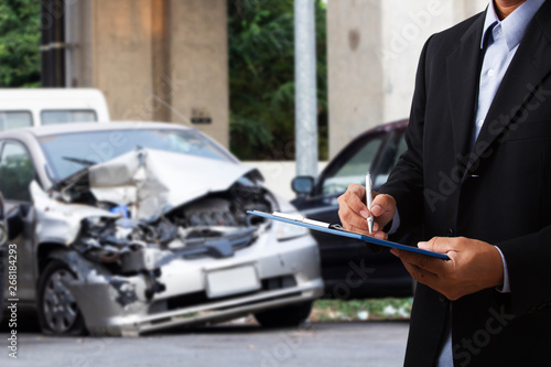 Car insurance officer writing on clipboard while insurance agent examining black car after accident.