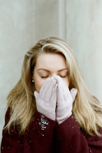 Young Woman Closes Her Face With Hands In Mittens