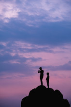 Two People Standing On A Rock At Sunset.