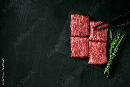 Premium raw Black Angus beef minute steak on Black wooden background Wallpaper Mural