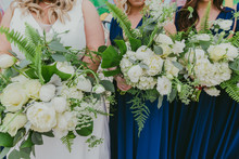 Bride And Bridesmaids Holding Bouquets With White Beautiful Flowers