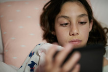 Girl Reading Kindle In Cozy Bed