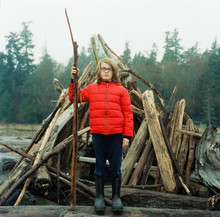 Boy Stands Guard With Stick In Front Of Driftwood Castle
