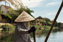 Unrecognizable Vietnamese Woman On A Boat Rowing.
