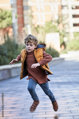 Six year old boy running after a ball in a city square or park