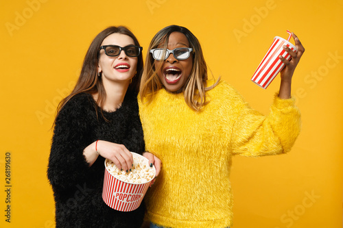Two women friends european and african american in black yellow clothes hold bucket of popcorn isolated on bright orange wall background, studio portrait Fototapeta