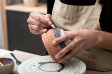 Artisan Decorating Clay Pot With Tool