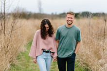 Cute Young Couple Walking In A Field
