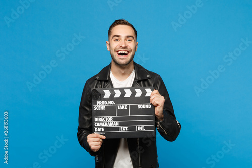 Fototapeta Handsome stylish young unshaven man in black jacket white t-shirt hold in hand film making clapperboard isolated on blue wall background studio portrait