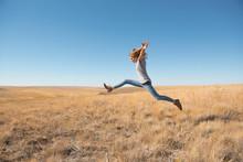 Woman Leaping In Field