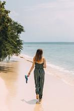 Woman Walking On A Tropical Beach