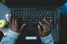 Young African Woman Typing On The Laptop Keyboard.