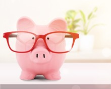 Piggy Bank In Red Glasses On W...