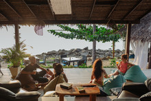 Group Of Friends In A Beach Bar Overlooking The Ocean