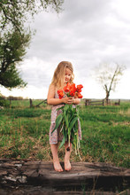 Pretty Girl Holding Pulled Up Red Tulips On A Cloudy Day.