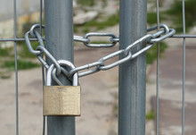 A Padlock With A Steel Chain Keeping A Iron Fence Closed.