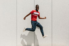 Cheerful Black Man Jumping In The Street