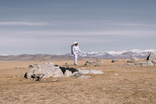 Astronaut Walking On Valley With Stones