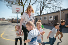 Woman With Kids On Outside On School Playground