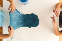 Above Shot Of Child's Hands Playing With Slime