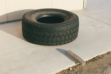 Discarded Truck Tire, Circle Of Rusty Metal And Slab Of Wood On Sidewalk