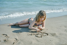 Little Blond Girl Playing With The Sand And Water Of The Beach