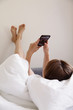 Woman with smartphone relaxing in bed