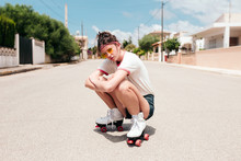 Portrait Of Young Woman With Skates Crouching On Road