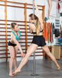 Pole dance instructor helping girl