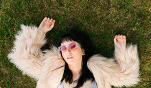 Female Laying Down In Grass With Sunglasses On