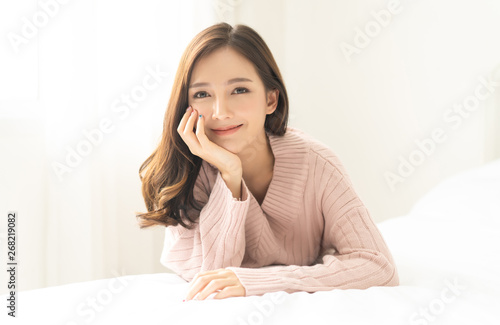 Fototapeta  Portrait of young Asian woman smiling friendly and looking at camera in living room