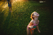 A Young Girl Wearing Bathing Suit Playing On The Grass With Sprinkler