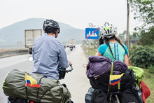 Couple Travelling By Bycicle Stopped On Road.