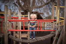 Happy Active Toddler Jumping On Colorful Playground Structure