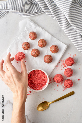 Overhead view of woman's hand preparing strawberry oat energy balls