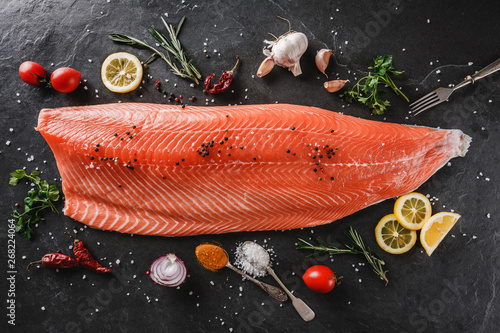Fotografia Fresh raw salmon fish steak with spices on dark stone background