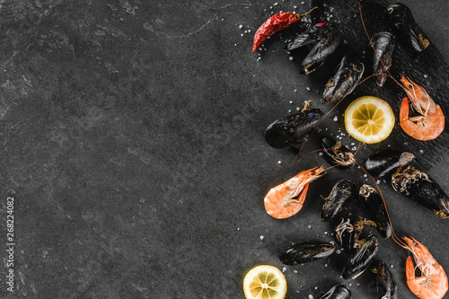 Valokuva  Fresh raw mussels and shrimp with spices and lemon on dark stone background