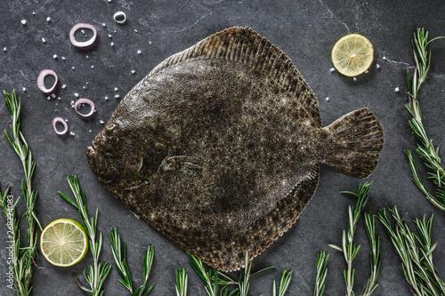 Photo  Raw whole flounder fish with rosemary on dark stone background