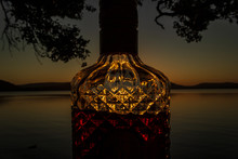 Beautiful Rum Bottle Full With Rum Holding In Front Of A Sunset Over Watson Taylors Lake At Crowdy Bay National Park, New South Wales, Australia