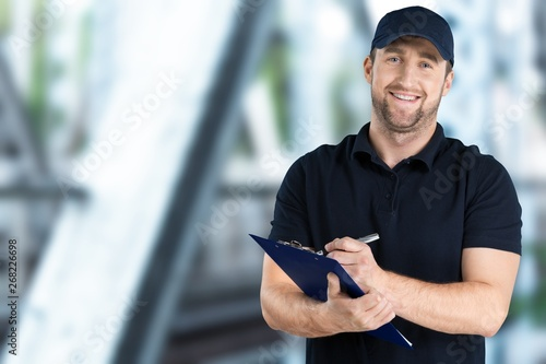 Fotografía  Delivery man with clipboard on light background