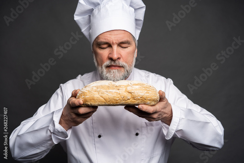 Photo  Portrait of a male chef cook smelling fresh bread against black background