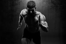 Muscular Men In Running Motion. Handsome Male Athlete Sprinting