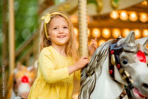 Obraz na plátně Adorable little girl near the carousel outdoors in Paris, baby girl on the carousel, Happy healthy baby child having fun outdoors on sunny day