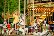 Adorable Little Girl Near The Carousel Outdoors In Paris, Baby Girl On The Carousel, Happy Healthy Baby Child Having Fun Outdoors On Sunny Day. Family Weekend Or Vacations