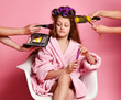 Leinwandbild Motiv Exacting young lady teen girl in spa salon evaluates makeup offered to her while making hair style and manicure on pink