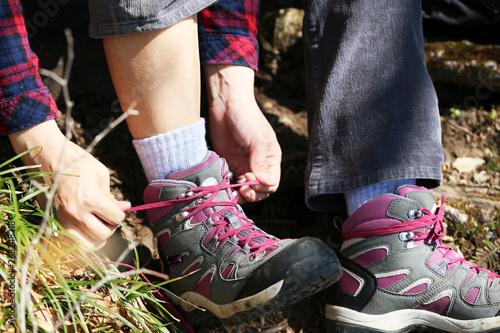 登山道でトレッキングシューズの紐を結び直す女性