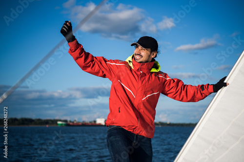 Fotografia Young man skipper in red windbreaker and black cap sets the sails on a sailing y