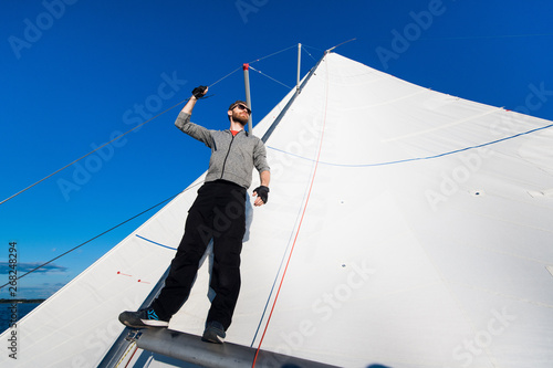 Fototapety, obrazy: Yacht captain with a beard stands on sail boom on a sailing yacht, holding the rope in his hand and smiling, feeling happy. Adult yachtsman travelling around the world. Copy space
