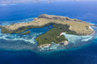 Seen from a bird's eye view, a rugged island is surrounded by a mangrove and reef in Komodo National Park, Indonesia. This tropical area is known for its marine biodiversity as well as its dragons.